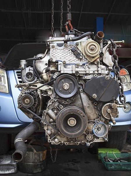 Older diesel engine hanging in front of newer car