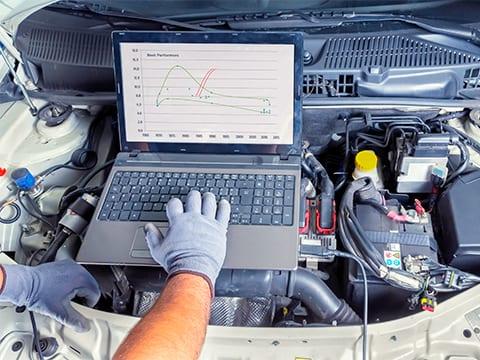 Technician using running diagnostics on an engine.