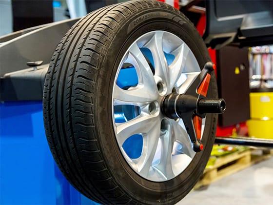 Car wheel on blue wheel balancing device