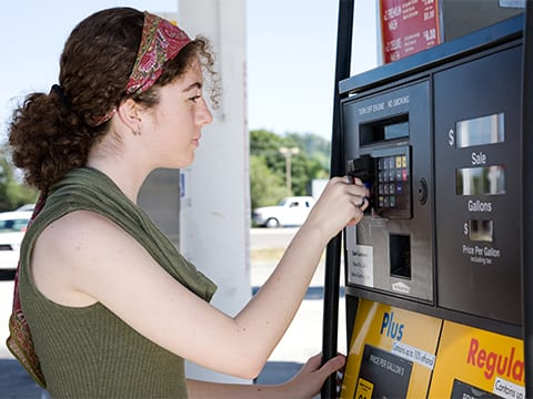 A woman using her credit car to purchase gas at a pump